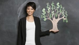 Happy Asian Business woman in front of chalk money tree drawing on blackboard.